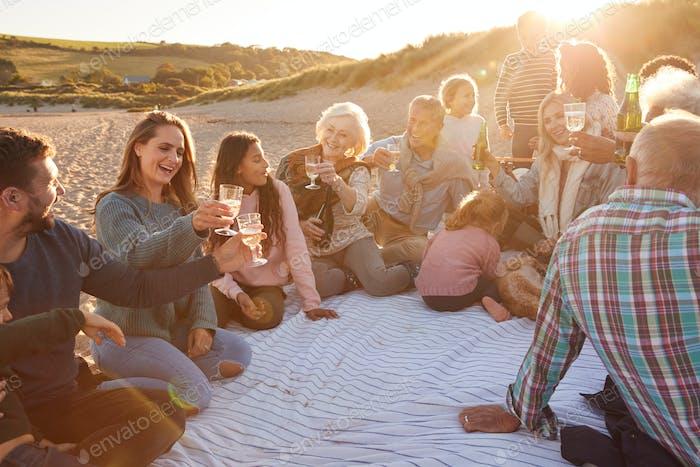 Mehrgenerationsfamilie, die einen Toast mit Alkohol im Winter Beach Urlaub machen