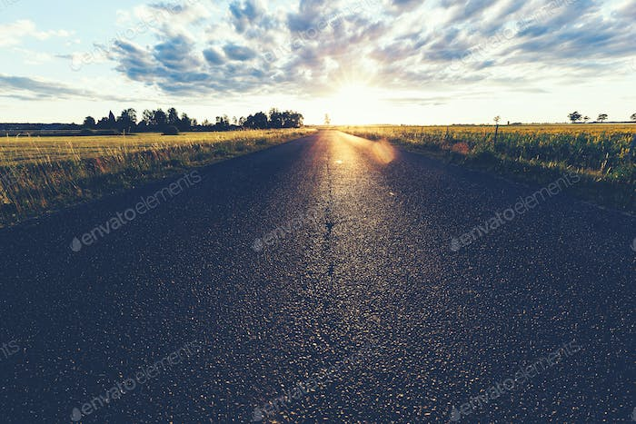 Asphalt country road, a grass field and sunset.