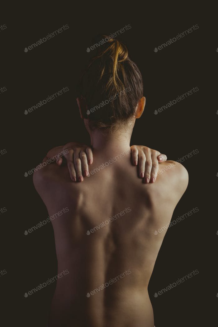 Nude woman with a shoulder injury on black background