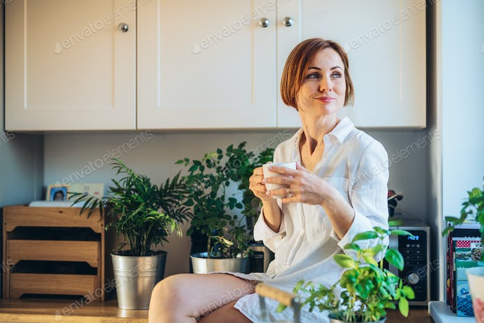 A young woman sitting on worktop indoors in kitchen, holding a cup of coffee.