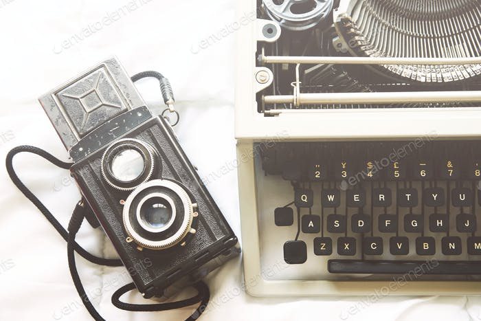 Vintage typewriter and camera on  white background.