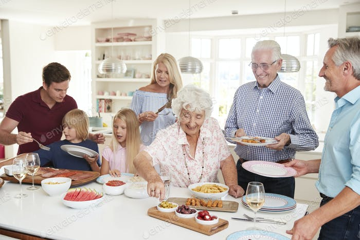Multi-Generation Family And Friends Eating Food In Kitchen At Celebration Party