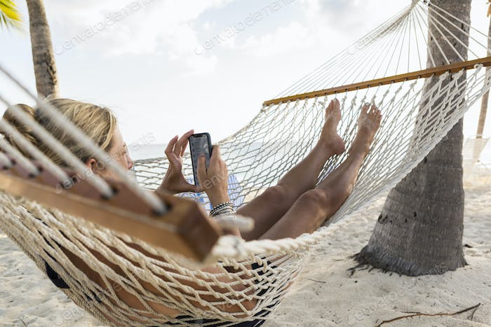 woman in hammock  using her smart phone