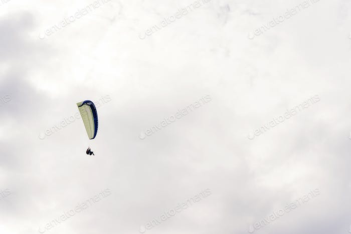 parachute skydiver flying in clouds, travel adventure concept, space for text