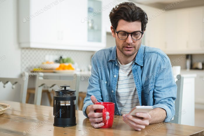 Man using mobile phone while having coffee in kitchen at home