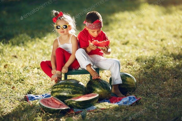 Niedliche kleine Kinder mit Wassermelonen in einem Park