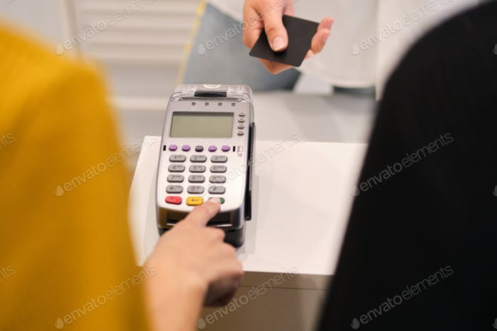 Close up customer paying with credit card in store