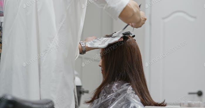 Haar-Stylist Anwendung Haarfärbemittel, um den Haarton in der asiatischen Friseur aufzuhellen