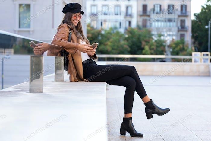Hübsche junge Frau, die ihr Handy benutzt, während sie auf der Straße sitzt.