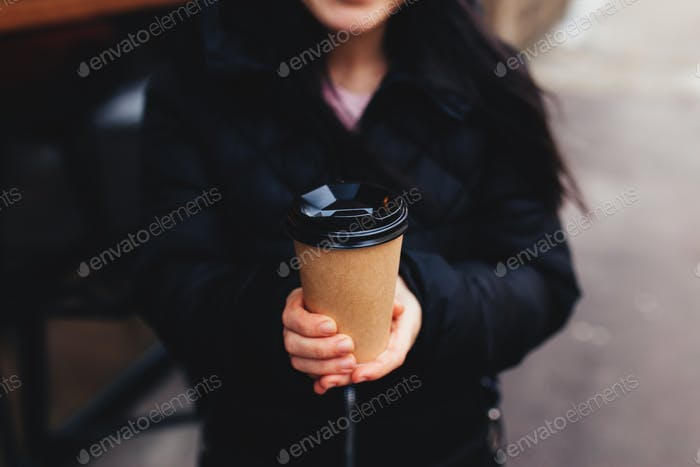 Girl holds a paper cup of coffee in hand near cafe