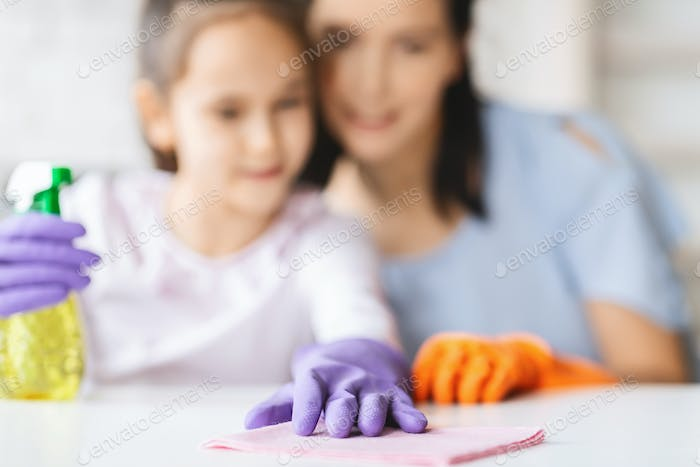 Housekeeping background. Mother and daughter cleaning table surface with rag