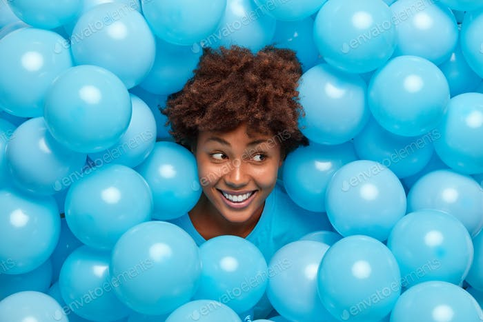Glad brunette young African American woman with curly hair sticks out head through inflated blue bal