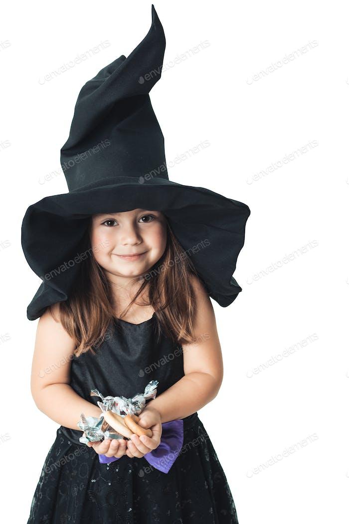 kleine Hexe zeigt die gesammelten Süßigkeiten