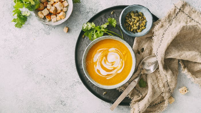Pumpkin soup in a bowl with cream