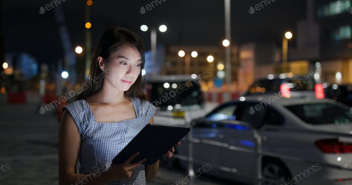 Businesswoman work on tablet computer at night