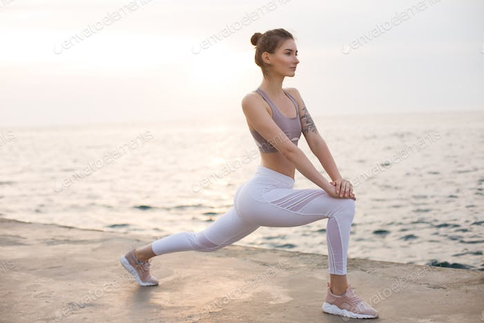Nice girl in sporty top and white leggings practicing yoga with