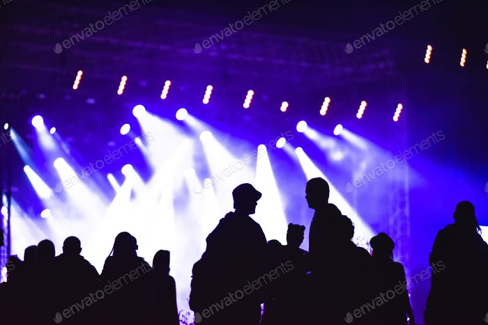 Group of friends enjoying music festival together. Silhouette of friends socializing at a concert