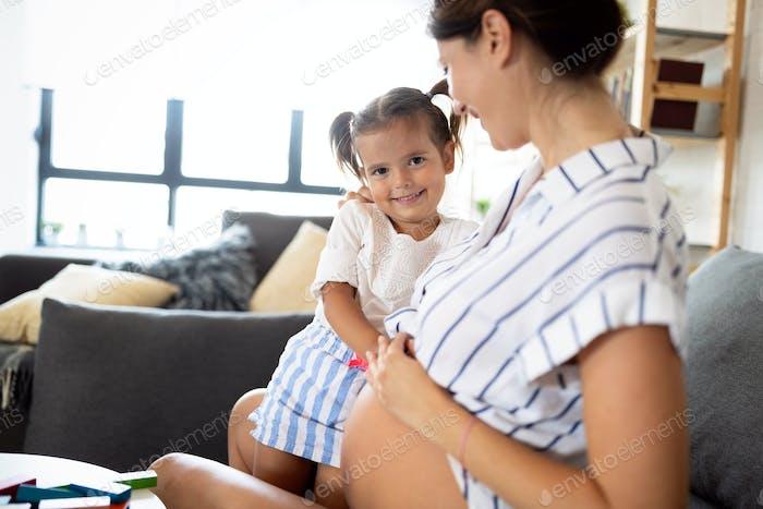 Glückliche Familie, Zusammengehörigkeit, Liebe. Schöne schwangere Mutter mit niedlichen Kind