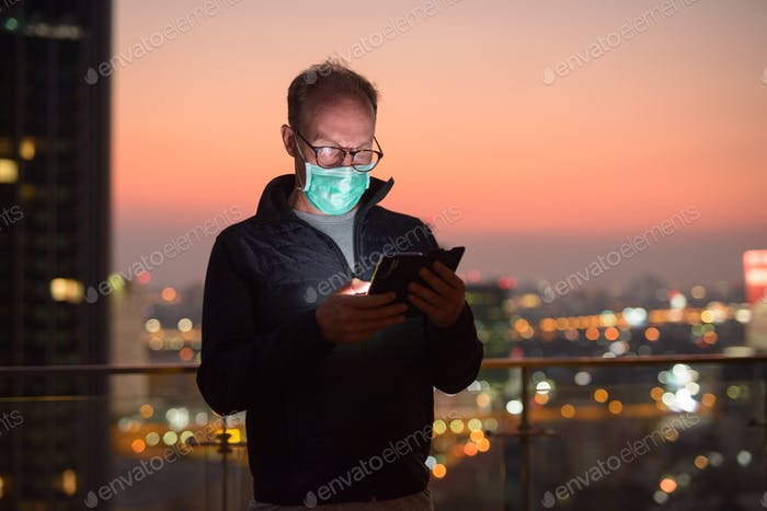 Mature man with mask using phone against view of the city at night
