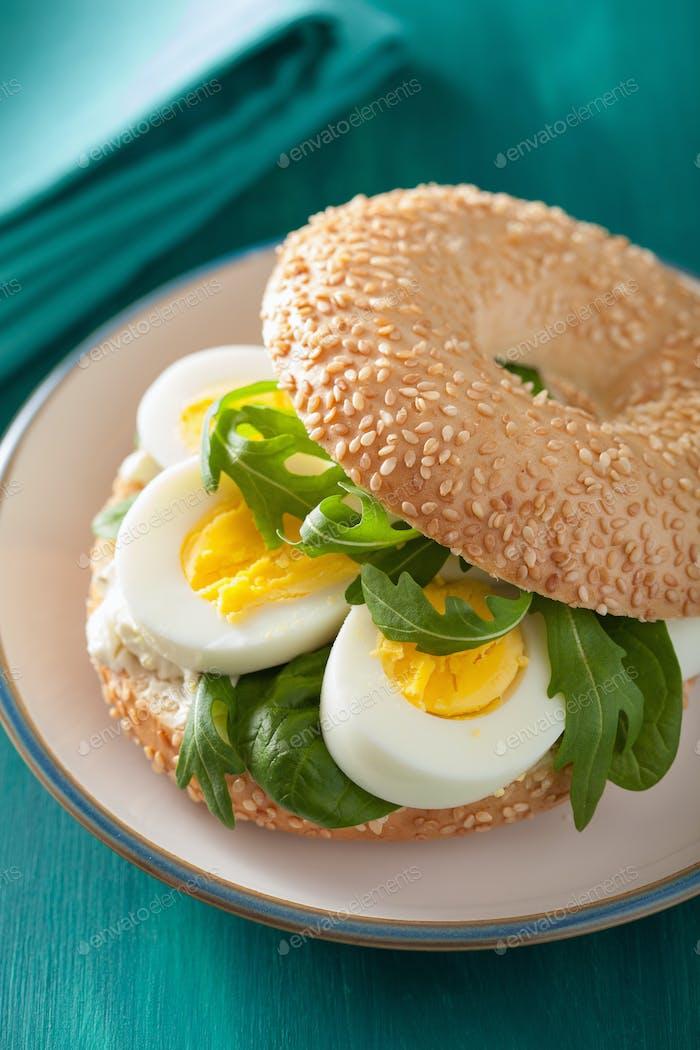 sándwich de desayuno en bagel con huevo crema de queso rúcula