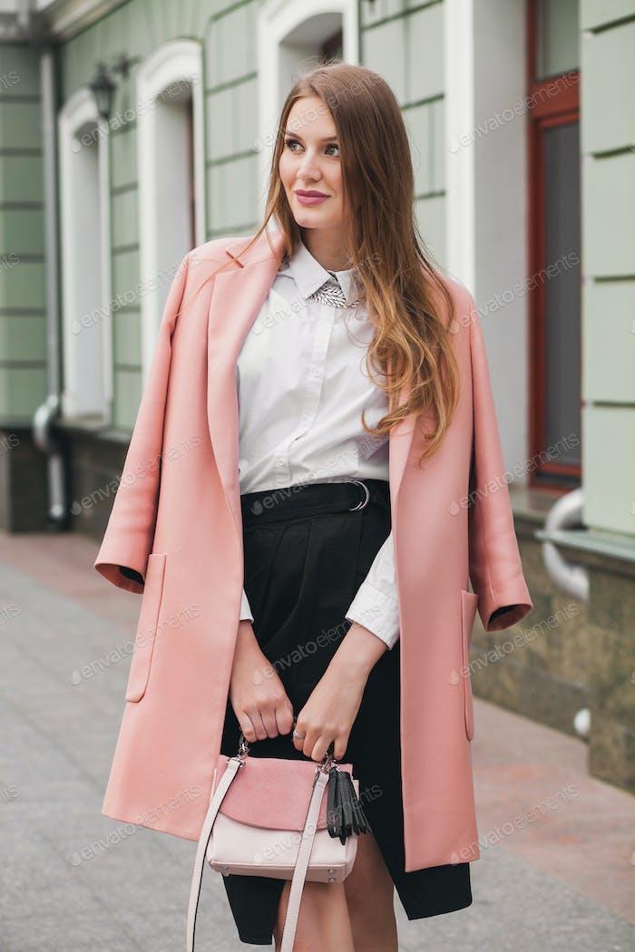 young stylish beautiful woman walking in street, wearing pink coat