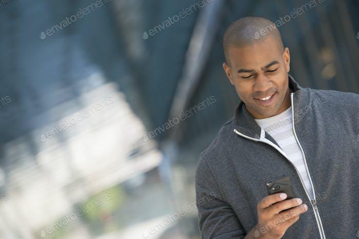 Ein Mann in einem grauen Reißverschluss Sweatshirt mit seinem Smartphone