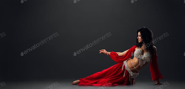 Woman in red arabic dress dancing oriental dances in stalls