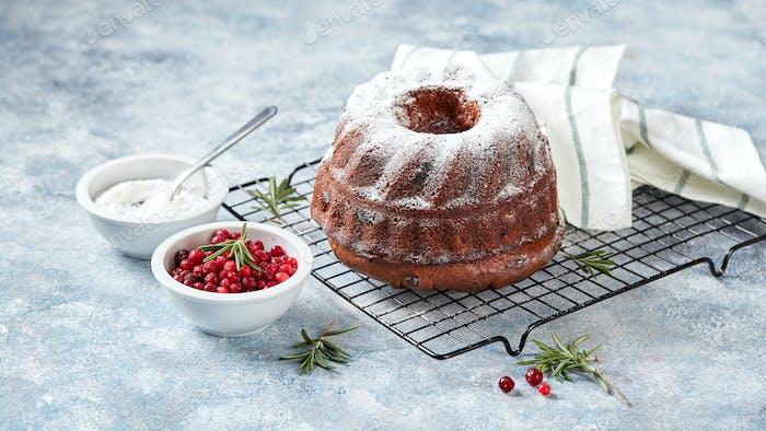 Schokoladenkuchen bestreut mit Puderzucker auf einem Metalldrahtgitter, Puderzucker und Preiselbeeren