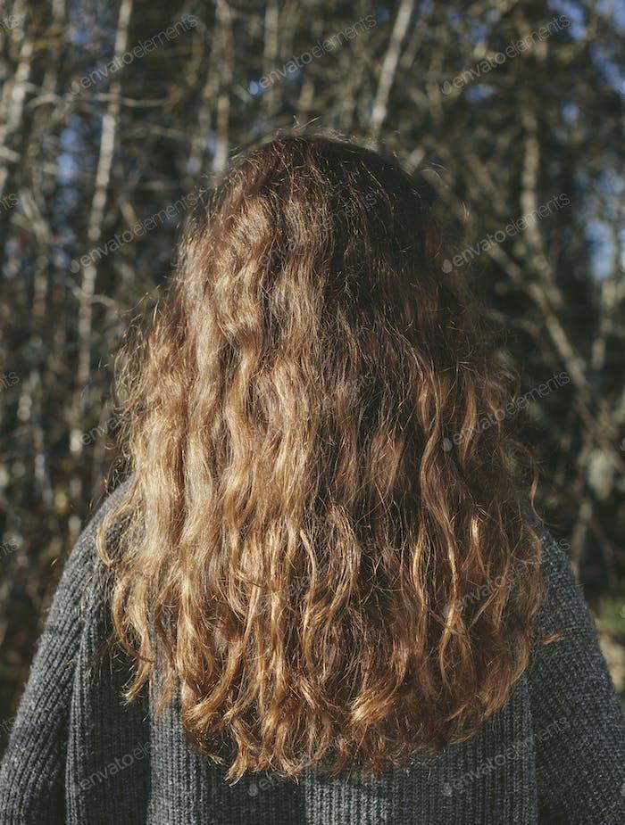 Blick von hinten auf Teenager-Mädchen mit langen, welligen, braunen Haaren