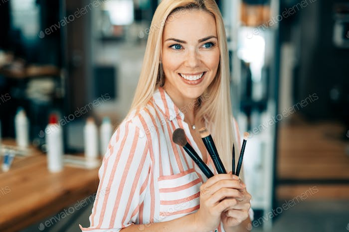 Portrait of the beautiful woman with make-up brushes near attractive face