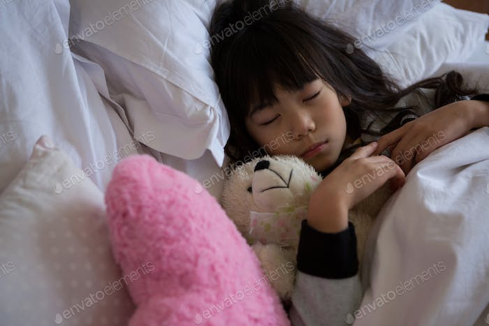 Girl with toys sleeping in bedroom