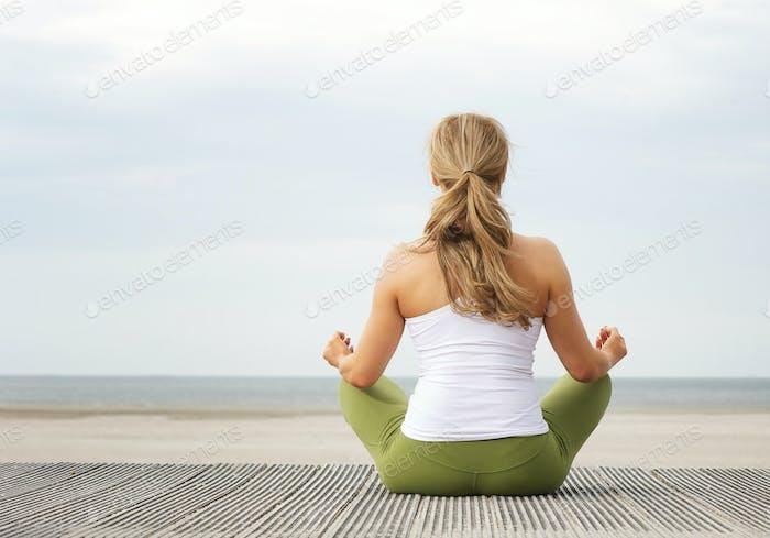 Vista trasera Vertical de Mujer joven sentada en Playa en postura de yoga