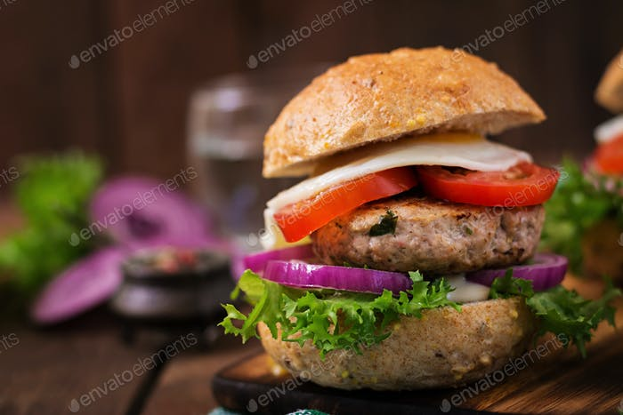 Hamburger (Sandwich) with chicken burger, lettuce, tomato, fried egg and tartar sauce