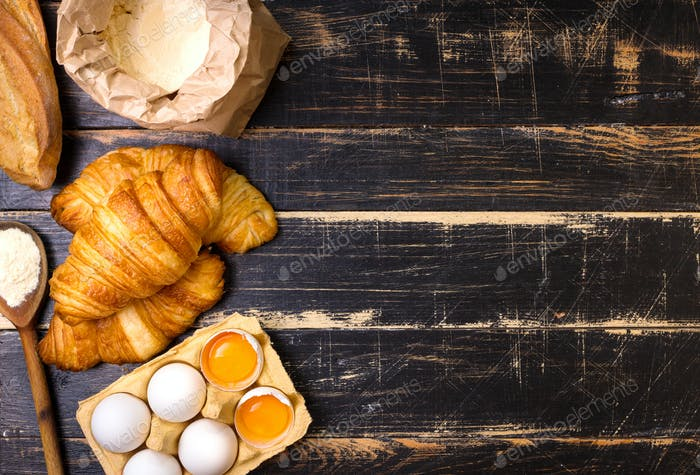 Croissants, baguette, flour, eggs, spoon background