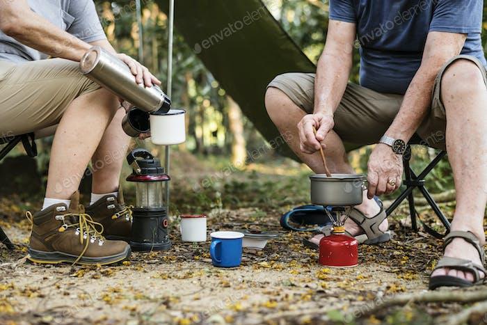 Reifer Mann Kochen auf einem Campingplatz