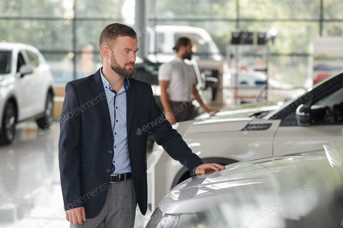 Men observing automobiles in car center