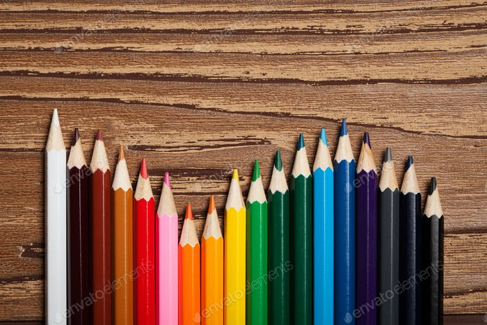 Many Different Colored Pencils On Wooden Table.