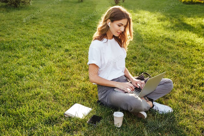 Photo of european woman 20s sitting on green grass in park with