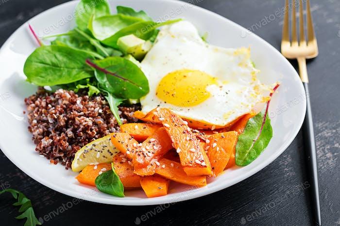 Breakfast with quinoa, fried sliced pumpkin, avocado and fried egg.