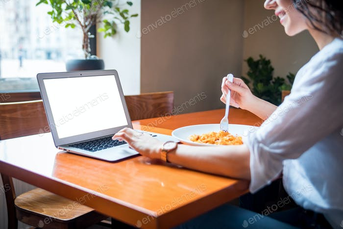 Пустой пустой экран ноутбука, Молодая женщина, работающая на компьютере в ресторане