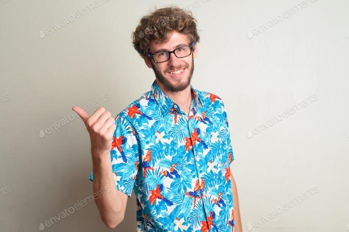 Glückliche junge bärtige Tourist Mann mit lockigem Haar geben Daumen nach oben