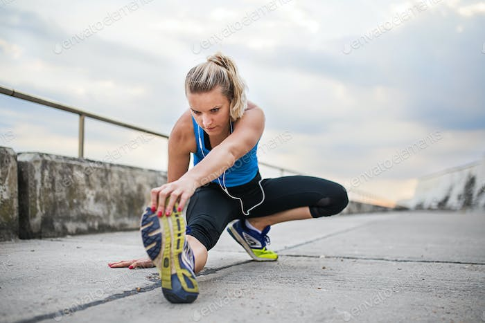 Young sporty woman runner with earphones stretching outside.