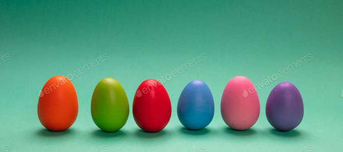 Easter eggs, pastel colors painted, standing in a row, green background