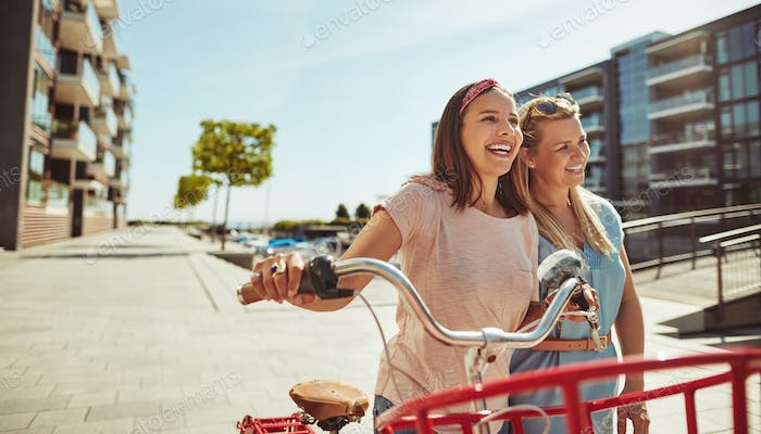 Two friends laughing while walking with their bicycle in summer