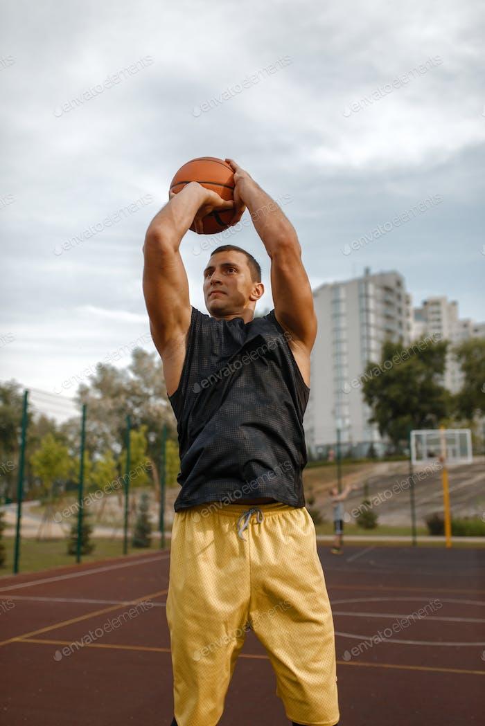 Jugador de baloncesto hace un tiro en la cancha al aire libre
