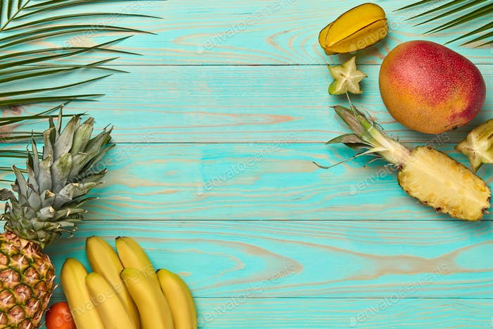 Corner frame from different tropical fruits and palm leaf on a blue wooden background with copy