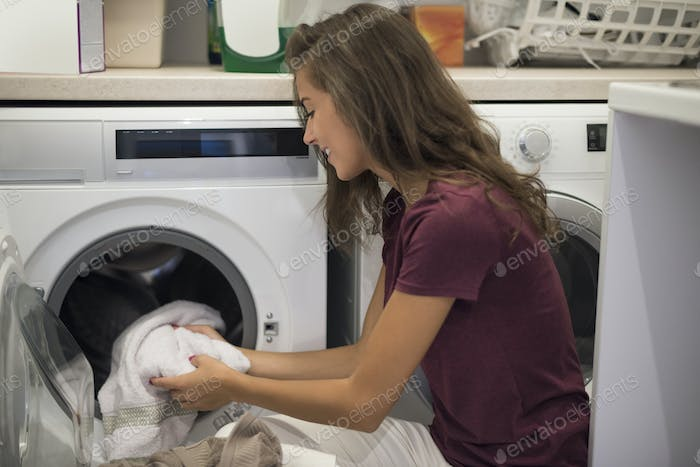 Woman turning on a washing machine