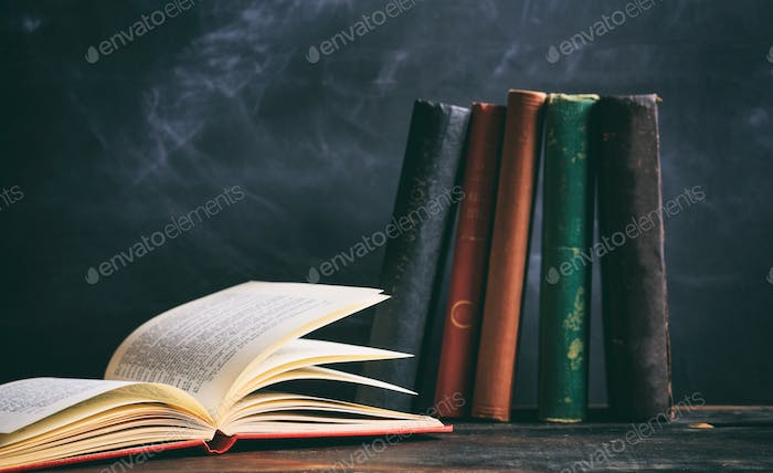Vintage books on blackboard background