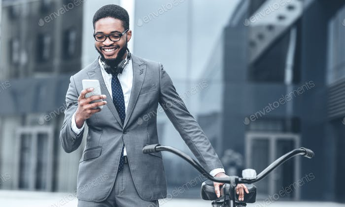 Businessman texting on phone, standing with bicycle