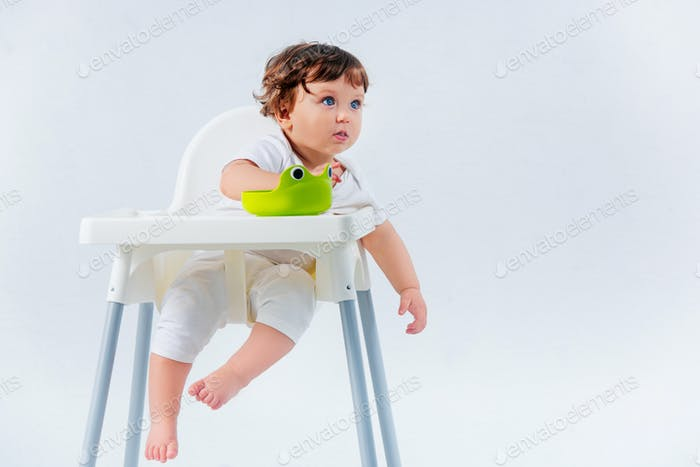 Happy baby boy sitting on studio background